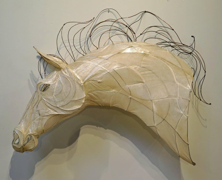 A stunning near life-sized sculpture of a horse head. Crafted from a translucent glazed white paper over a copper wire frame, the mane also of copper wire, bent and twisted, as if being blown by the wind.