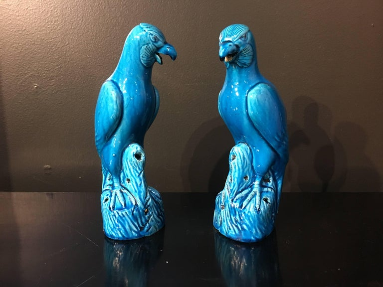 A pair of late 19th century Chinese export models of hawks. Well modeled and glazed all-over in a brilliant turquoise blue, the birds of prey perch upon rocky outcrops, with heads turned. They gaze intently outwards, beaks open in a triumphant