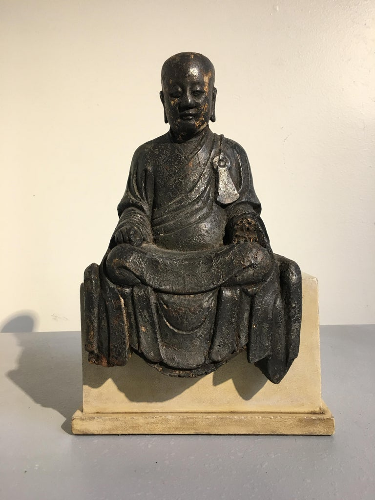 A serene and charming Chinese carved and lacquered wooden figure of an Arhat or Luohan, late Ming dynasty, circa 1600. The noble figure depicts and elderly disciple of the Buddha, known as a Luohan or Arhat. He is portrayed seated upon a platform