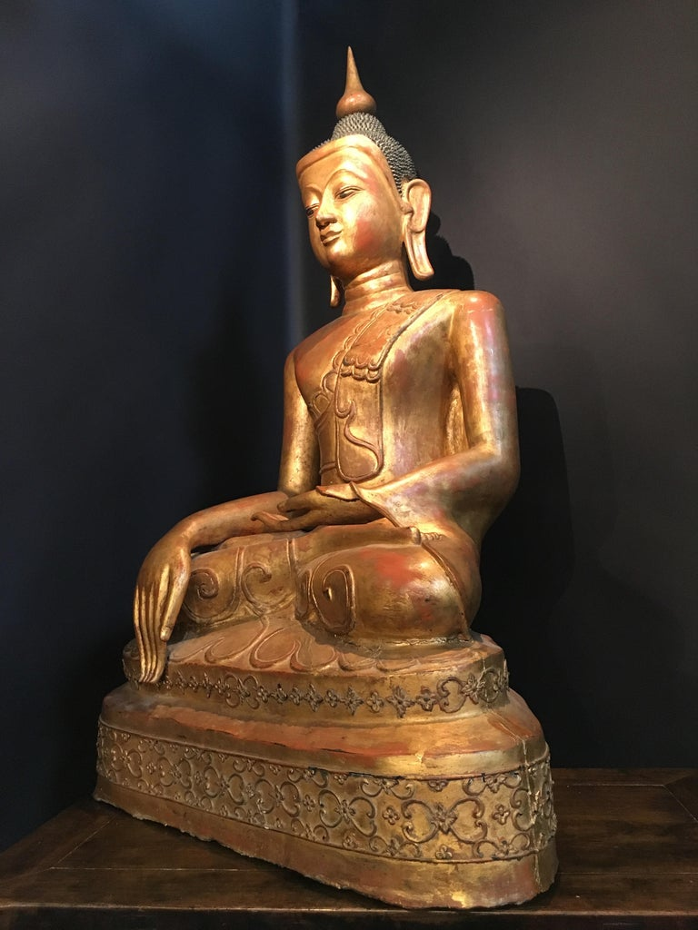 A large and impressive Burmese papier mâché gilt lacquer figure of the historical Buddha, Shakyamuni, Shan States, Burma (now Myanmar) circa 1880 - 1900. The Buddha sits in vajrasana upon a stepped platform, hands in bhumisparsha, one hand upturned