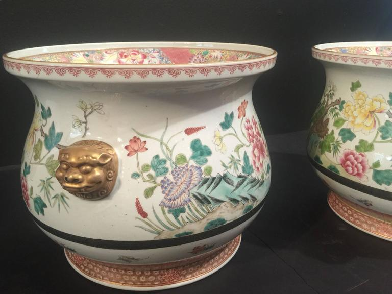 A stunning pair of Chinese porcelain cachepots, finely painted in famille rose enamels. The bulbous body features a Traditional Design of blossoming flowers, including peony, lotus, chrysanthemum and dogwood, with a pair gilt lion mask handles. The