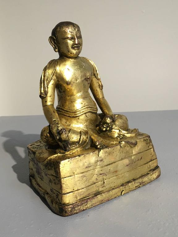 An unusual Tibetan gilt bronze figure of an arhat, one of the original disciples of the Buddha. This figure has been tentatively identified as Bakula, based on the fruit he holds in one hand, and the phial of amarita, the elixir of immortality, in