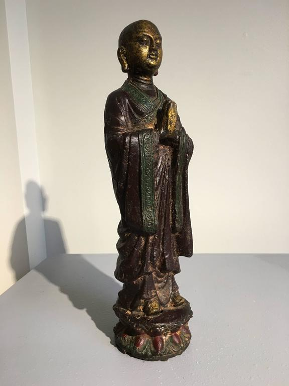 Ananda is portrayed in a typical fashion, as a youthful monk with a shaved head and dressed in simple robes. He stands upon a double lotus pedestal with hands clasped in front of him, eyes cast downwards, a serene expression upon his face. 