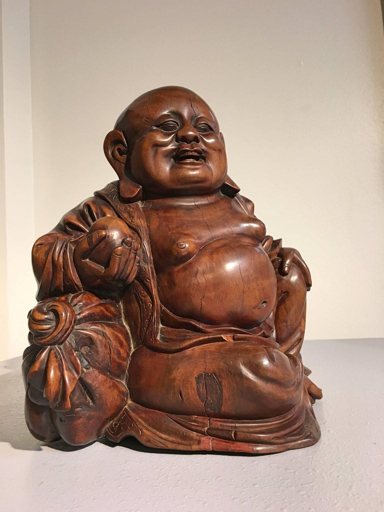 A late Qing dynasty well carved hardwood carved figure of Budai. Carved from an extremely dense hardwood, with a rich, well figured grain that shimmers in the light. The top of his head displaying a warm and shiny patina form years of people rubbing