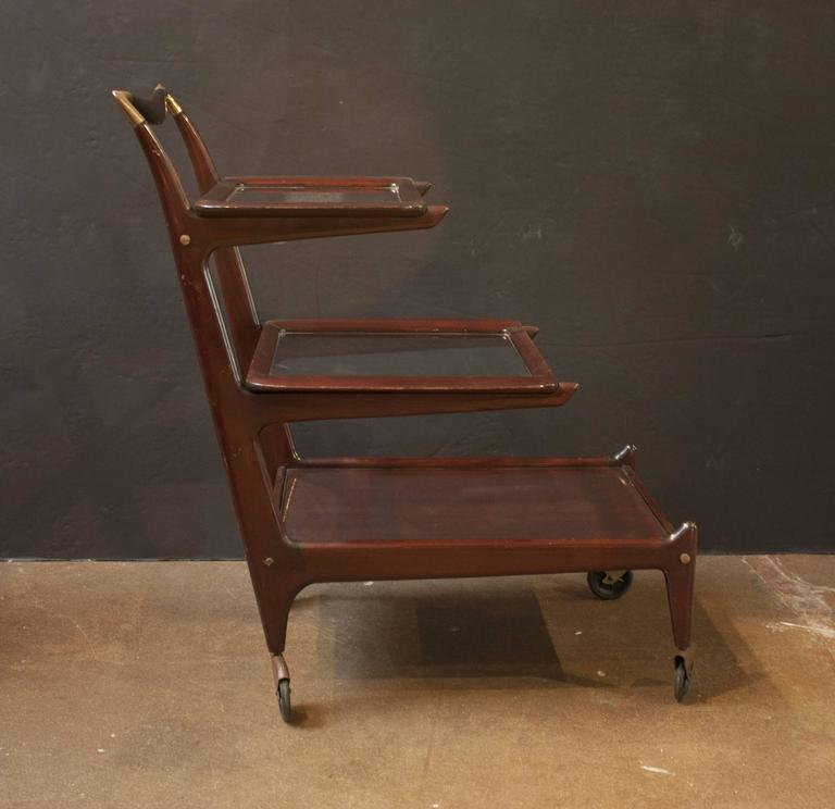 An Italian, Mid-Century three-tiered rosewood bar cart with two removable serving trays by Cesare Lacca for Cassina. 
