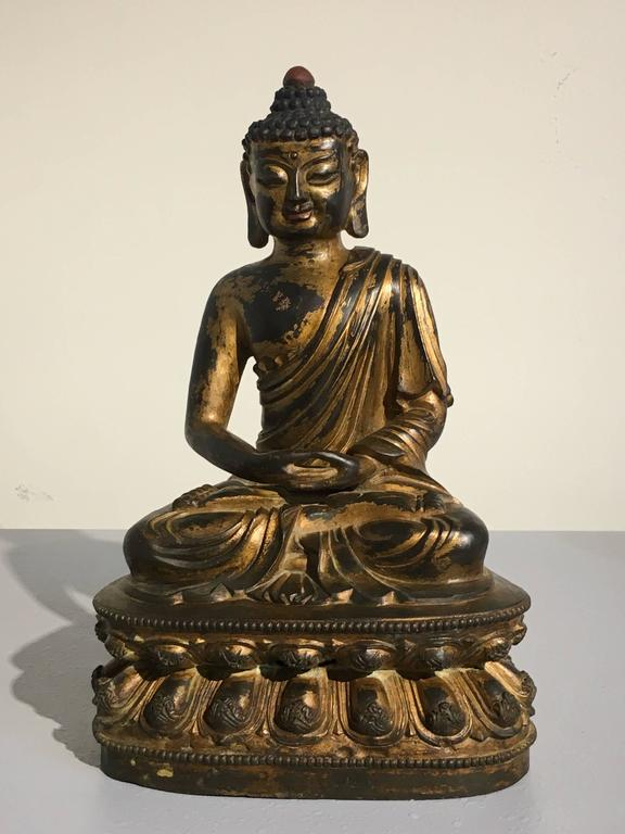 A heavy and finely cast gilt bronze image of the Buddha Amitabha, 20th century, China.   The Buddha of immeasurable light sits in vajrasana upon a double lotus pedestal, hands in dhayana mudra. He wears a kasaya wrapped around his body and draped
