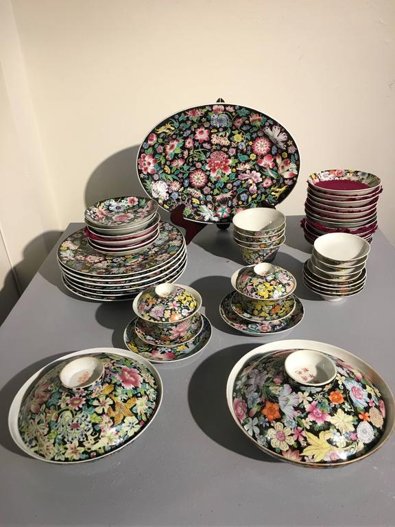 A large assembled set of Chinese porcelain mille fleur wares. The set featuring a full tea service, as well as various plates, cups, and saucers. All piece in the mille fleur, or thousand flowers, pattern, on a black ground. All pieces marked with