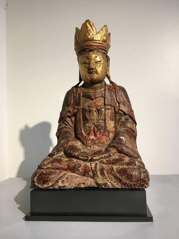A beautiful and serene Chinese Ming dynasty carved wood figure of the Buddha Amitayus, the Buddha of long life, and a form of Amitabha Buddha. He is seated in dhyanassana, dressed in loose fitting robes, and adorned with a five pointed crown and