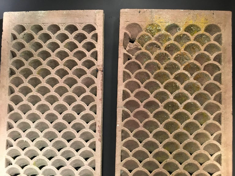 A stunning pair of Indian sandstone jali panels, carved, undercut, and pierced in a fish scale pattern.