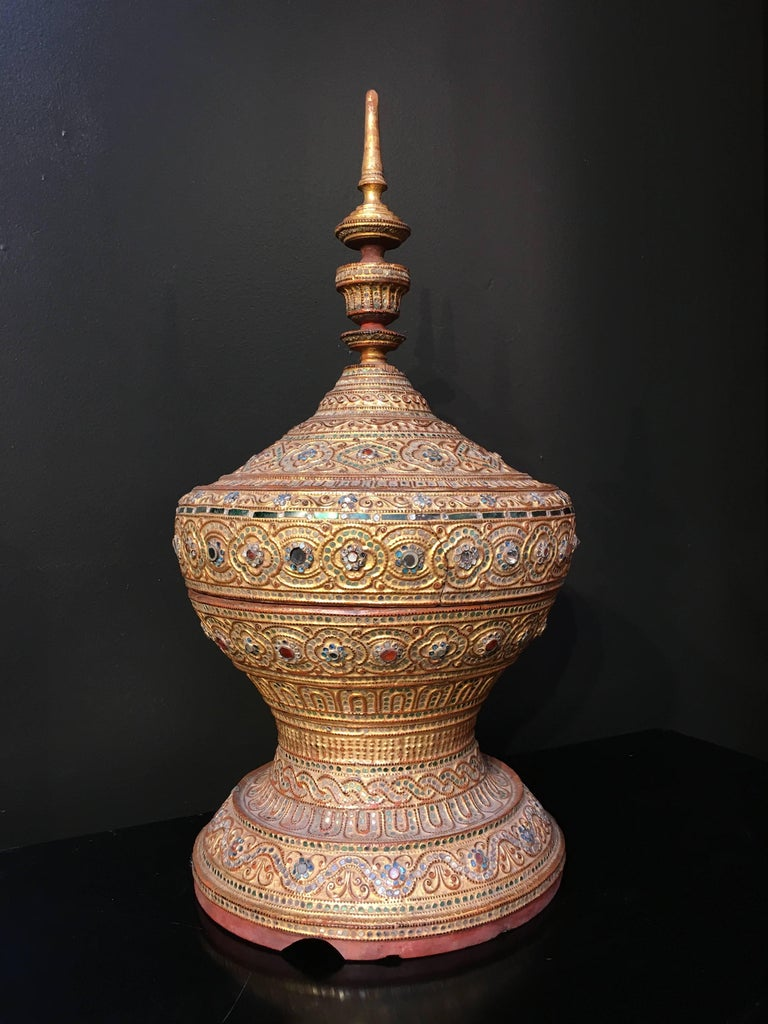 A resplendent Burmese Mandalay period offering vessel, called a hsun-ok, early 20th century. The shape is reminiscent of a stupa, a Buddhist architectural monument honouring a sacred site. Crafted from bamboo, overlaid with lacquer, gilt, and