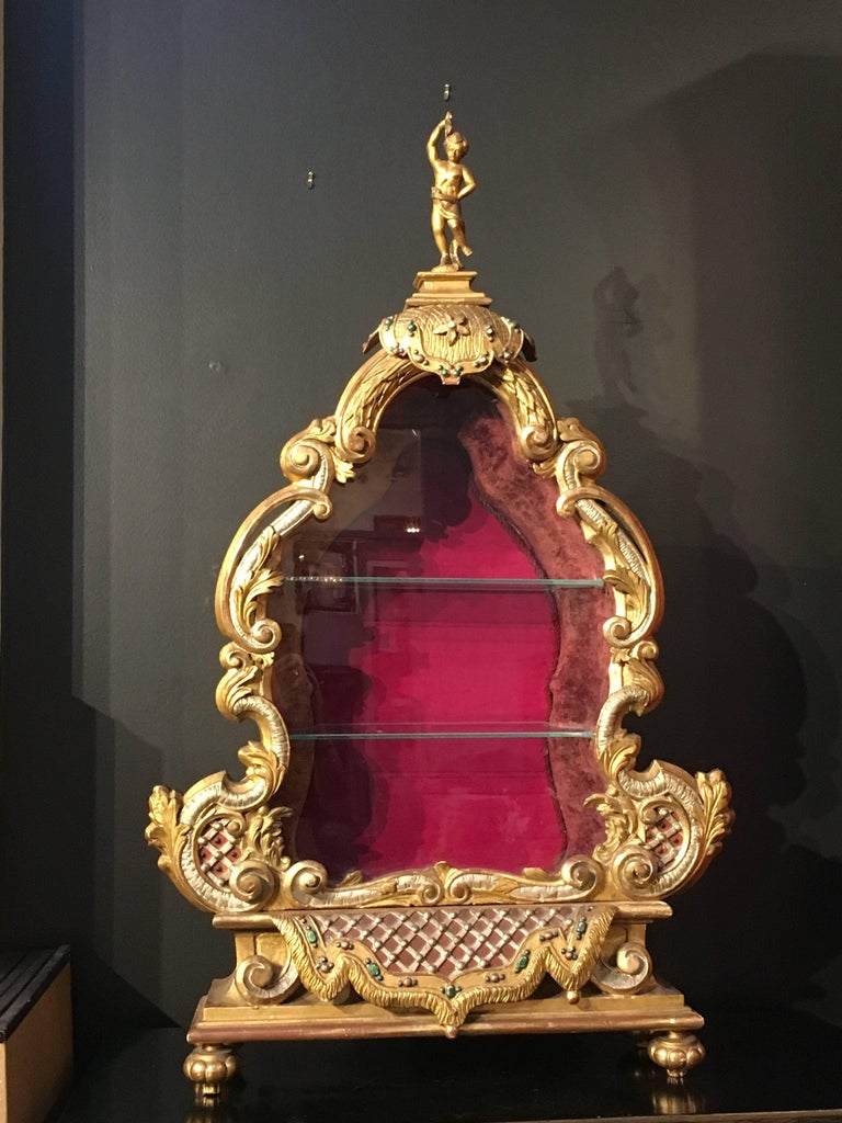 An elegant late 19th century Baroque style tabletop vitrine. The vitrine marvelously carved and richly gilt in the Baroque manner, with beautiful foliate scrollwork and polychrome detailing reminiscent of grotto architecture, all topped by a