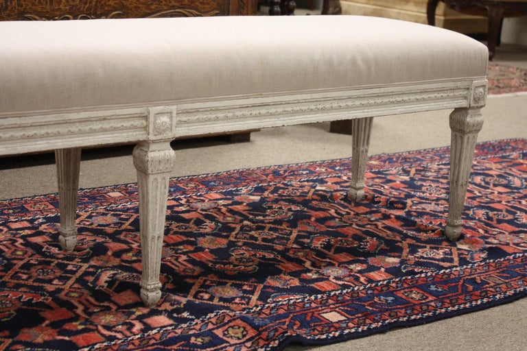 Louis XVI bench from France. Carved, circa 1880, the antique bench has six tapered legs, symmetrical carvings around the apron, and is reupholstered in a neutral. Due to its size and narrow profile, the bench would also make the perfect piece at the