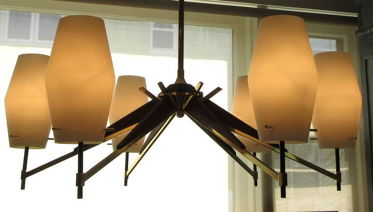 A large six-light Danish modern chandelier. Six arms of walnut and brass terminate with an opaque white glass cylinder form shade. The chandelier hangs from a brass rod. The sockets hold candelabra size bulbs. Pictured when lit is with 25 watt bulbs