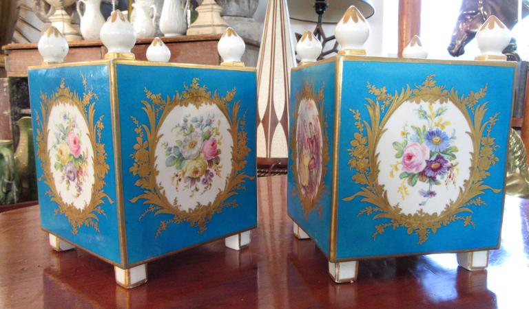 A pair of early Sevres (Vincennes) porcelain orange pots with the traditional blue turquoise background. Three sides are medallions of flowers while the Fourth is a romantic scene. All are surrounded by gilt foliage.