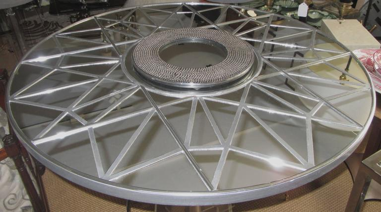 A large round mirror divided into geometric segments. The center is a circle of metal studs.