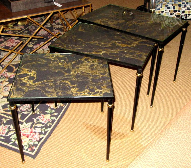 A set of three nesting/ stacking tables in black metal with brass accents and brass ball feet. The tops are clear glass with handmade marbleized black and gold paper below.