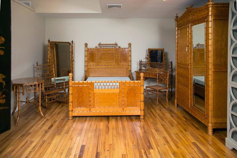 The principal piece in this rare collection of late 19th century golden stained bird's-eye maple faux bamboo bedroom furniture. The full size bed with a spindled crest, paneled head and foot-board, the uprights having ball finials with conforming