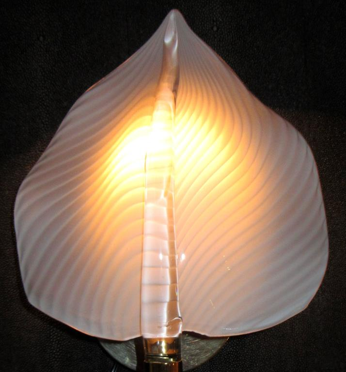 A pair 'two pairs available' of handblown Italian glass wall sconces in the form of leaves with a stem. The leaf shaped shade is a striated white and the