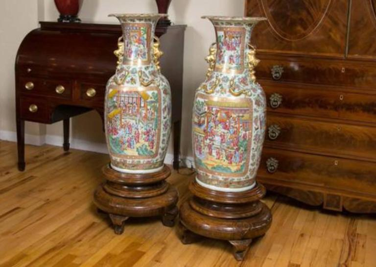 A fine pair of large Cantonese Famille Rose, specifically Rose Mandarin, vases. Of baluster form with a trumpet neck, dogs of fo handles, and raised gilt Chiang Dragon on the neck and shoulders. Polychrome enameled and gilded with scenes of court