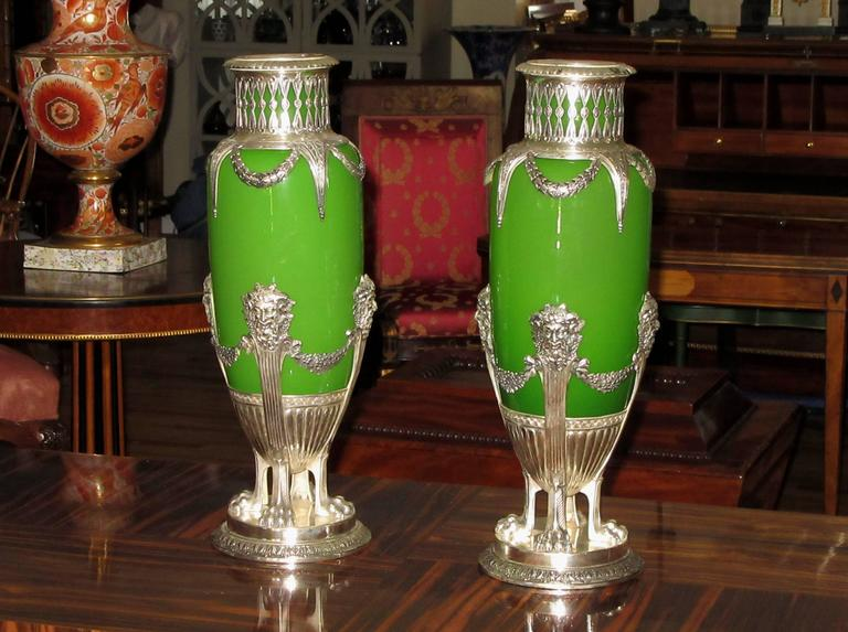 A pair of ovoid shaped vases in green opaline glass held in silvered metal mounts. Each vase is crowned with an openwork gallery that descends to the body of the vase in the form of draped laurel garlands. The body of each vase rests in a round base