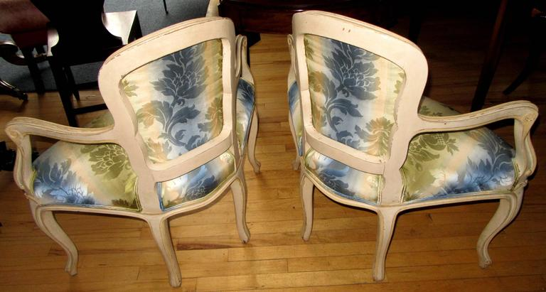A pair of Louis XV style cream painted corner chairs each with cartouche shaped padded backs and seats on cabriole legs terminating in scrolled feet.