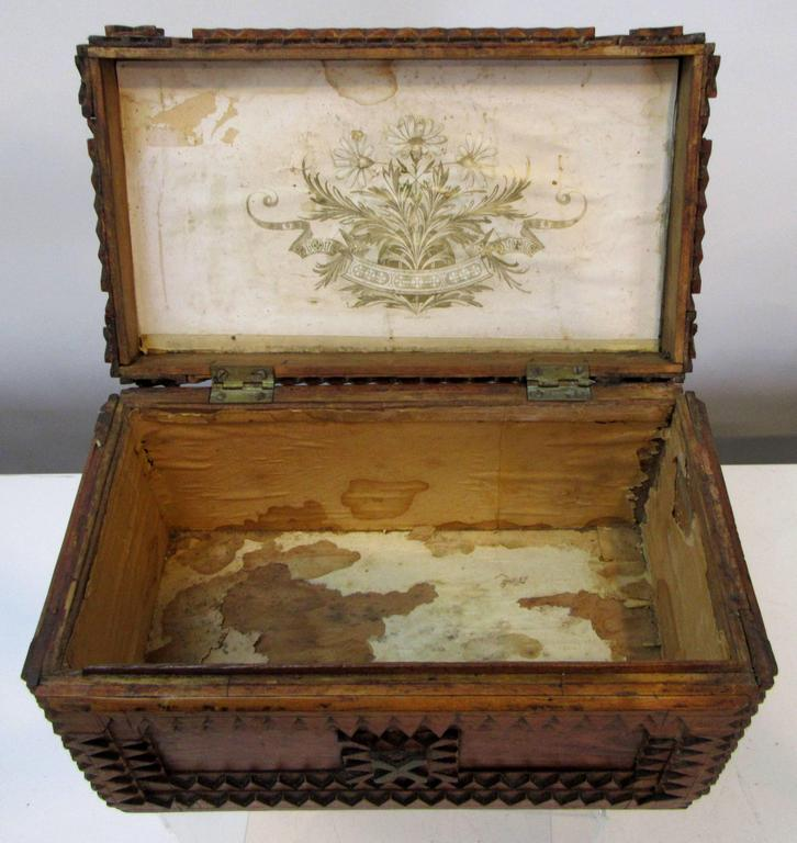 A hinged lid Tramp Art box made using a Schutz Marke Deponirt Razor Box from Germany. The inside of the lid is lined with a gold flower and banner pattern.