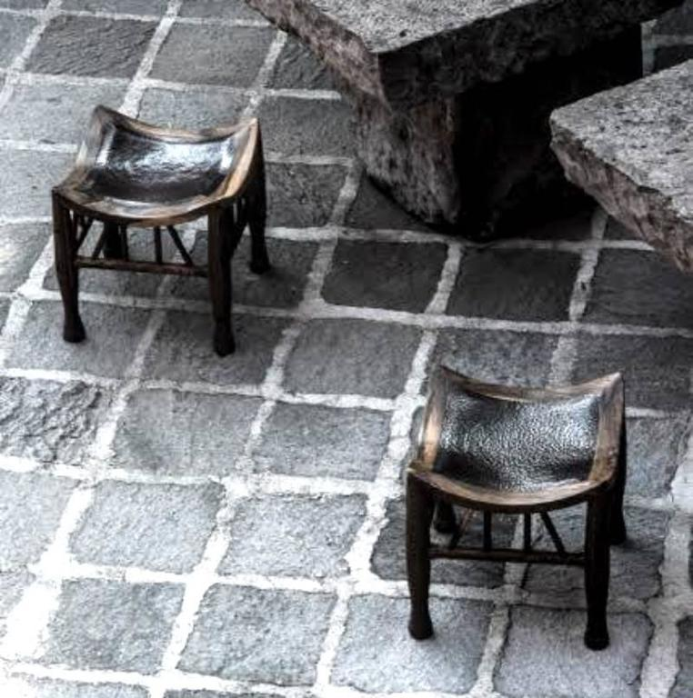 A pair of square tropical cueramo wood frame stools with seats of hammered copper. Designed by Miguel Angel Arregui and crafted by Mexican Artisans.