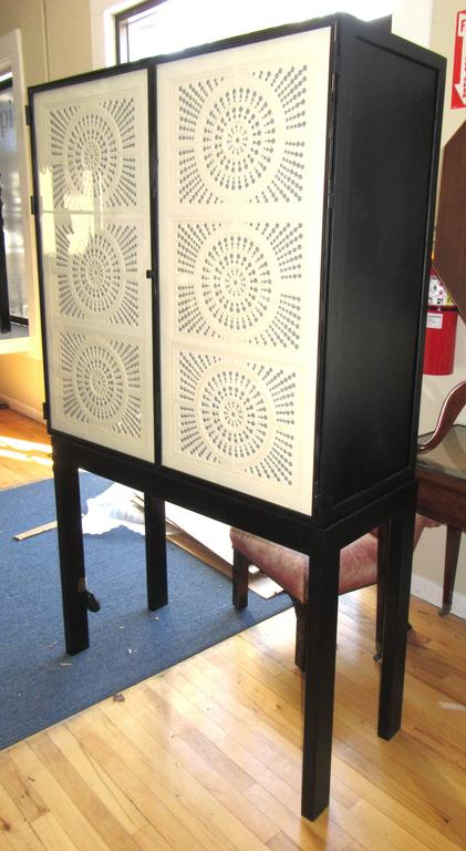 An iron frame cabinet on stand. The doors are glass, lined with intricately cut-out paper. The cut-out design allows the fabric lined interior to glow through. The shelves are removable glass. The cabinet is wired to light from the interior.