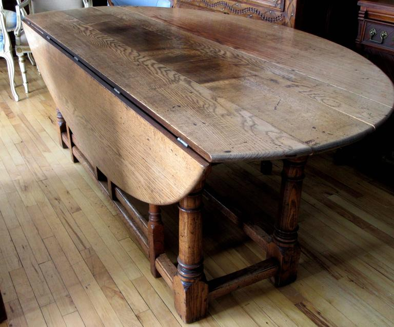 19th century English oak double gateleg hunt table, the rectangular top with rounded ends flanked with oval or D-shaped drops, above a scalloped apron and rising on turned legs conjoined by the box stretcher.