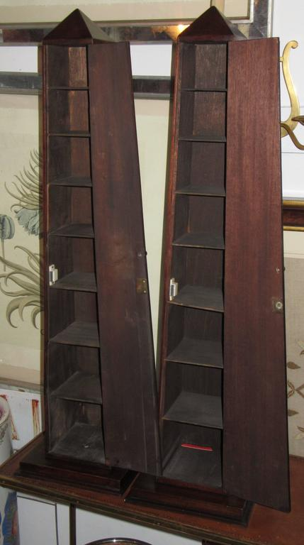 A pair of mahogany obelisks on platforms. One side opens to reveal graduated shelves.
