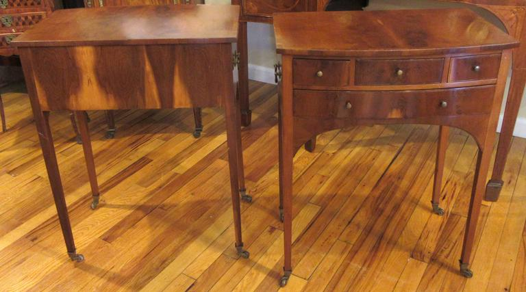 A pair of nicely proportioned four-drawer tables on brass casters. Flame mahogany veneer with original brass hardware.