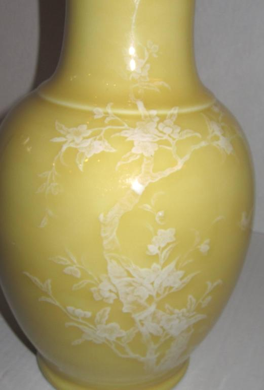 A porcelain high shine glazed vase with enamel hand painting of flowering trees and birds in textured relief.