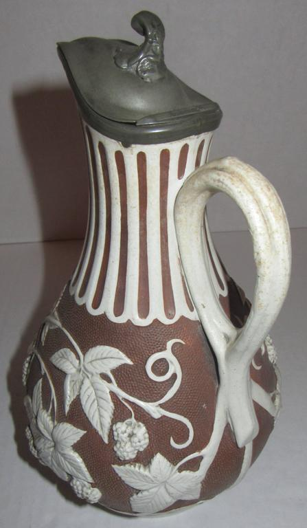 Blackberry on the vine, brown and white Parian ware pitcher with the original pewter lid. The marking dates it to being produced in England on January 18th, 1863.