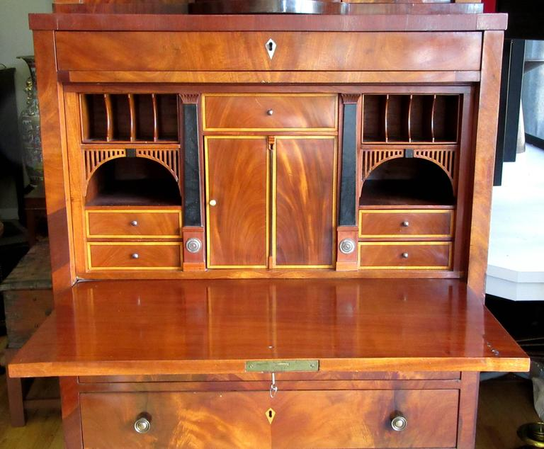 An early 19th century Biedermeier secretary in two parts. The upper consisting of a mirror backed rotunda of alabaster and marble columns which rotates to reveal five small drawers and curved compartments on either side. The lower portion holds a