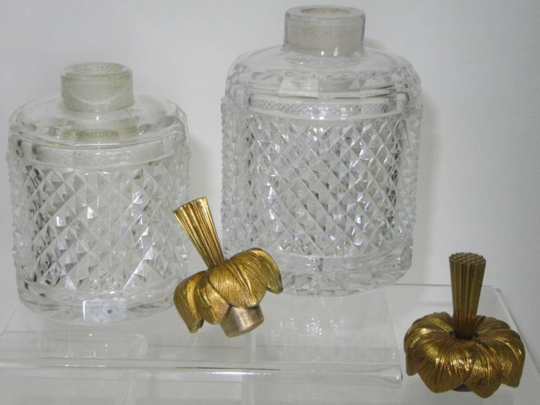 A large and a small, two round crystal bottles with bronze doré flower form stoppers.