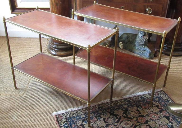 A pair of rectangular brass end tables with brown embossed leather shelves.