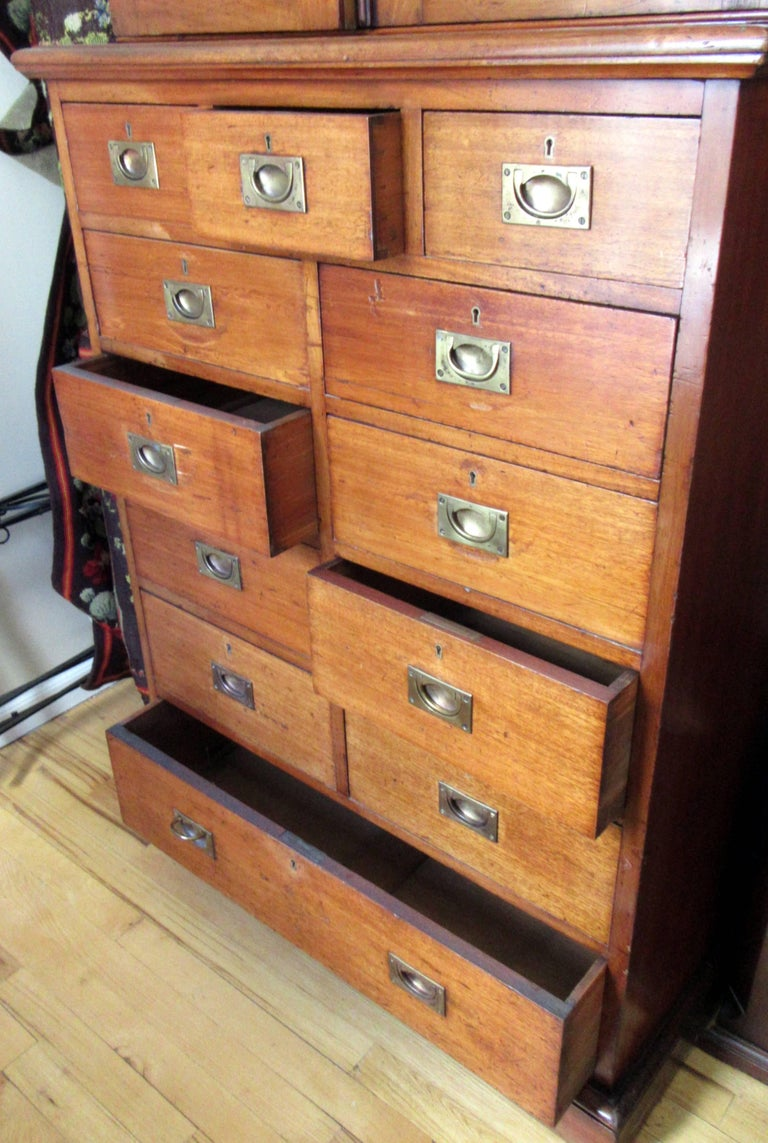 A multi drawer, brass handled Campaign chest beneath a two-door cabinet with three shelves.