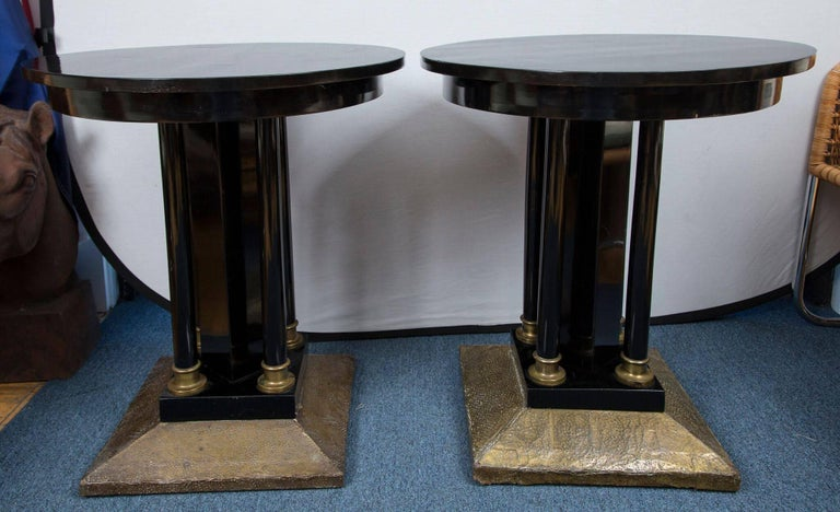 A pair of black lacquered wood tables with pedestal bases. The square foot of each base is mounted in hand-hammered brass and the pedestal columns sit in brass caps.