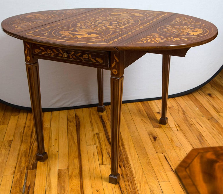 An extensively satinwood inlaid walnut drop-leaf table with tapered legs terminating in spade feet. I single long drawer opens on either end. When leaves are up the table is an oval of 46.5 inches in width. Measurements listed are at the leaves