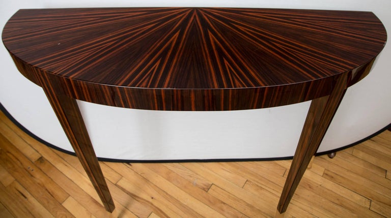 A pair of Macassar ebony veneer, high polish lacquered demilune consoles. Tall, tapered legs are fitted with brass sabots.