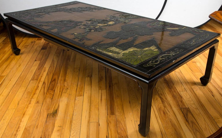 Two panels of a Chinese painted and lacquered folding screen now re-purposed as the top of a long rectangular low table.