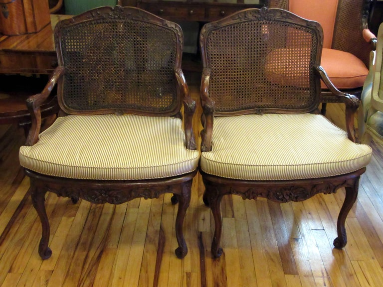 A pair of carved beechwood, caned back and seat armchairs with upholstered cushions. One chair is signed L. Cresson. During the 18th century the Cresson family produced a remarkable number of furniture makers. One of the most prominent Cressons was