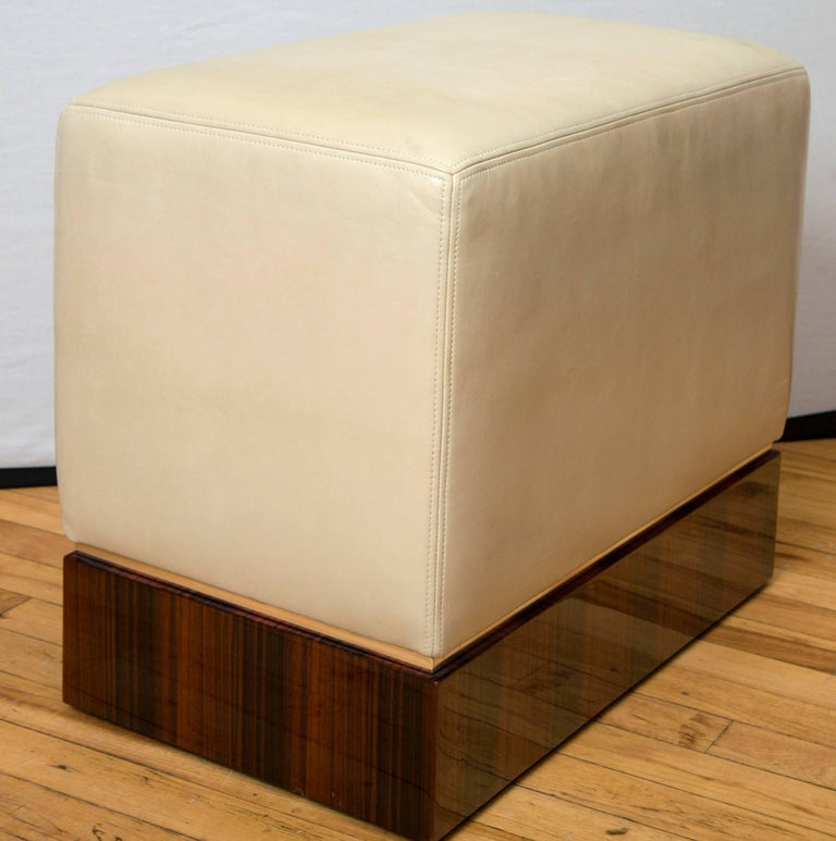 A pair of ottomans upholstered in creamy lambskin leather. Hidden casters allow for easy movement, while glossy Macassar ebony veneer bases create a polished finish.