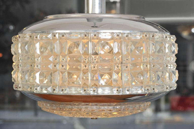 Glamorous chandelier with one main tier over a secondary one, both encrusted with cut-glass resembling faceted diamonds, supported by a chrome frame. (The height measurement below includes the supporting chrome rod).