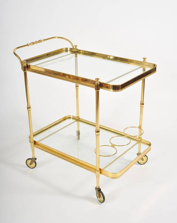 Brass drinks trolley with two glass shelves, curved corners and elegant handle. Brass holders to store bottles.