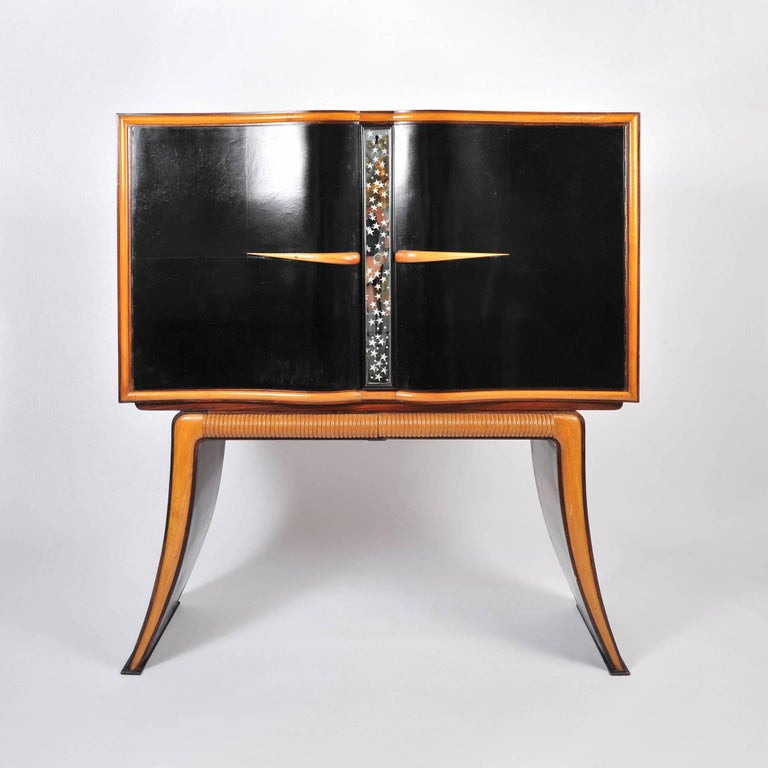 Spectacular drinks cabinet with dark mahogany doors opening to a dazzling world of night stars and dancing ladies entwined in nature. Exterior ebonised fruitwood doors are detailed in veneered mahogany and separated by a starry mirrored panel.