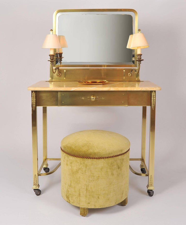Well-proportioned brass dressing table or vanity with honey-colored marble top, on wheels, with single drawer, integrated rectangular mirror and lamp holders.