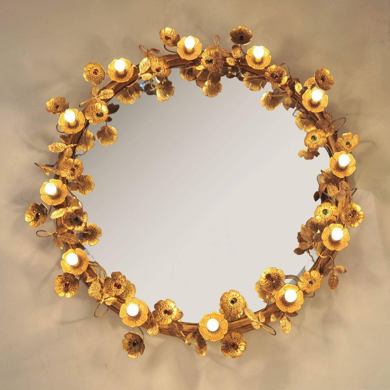 This glamorous wall mirror consists of delicate gold brass flowers and leaves that encircle the beveled mirror. Each flower is finished with a ruby or emerald centre unless it holds one of twelve subtle light-up flowers. It cannot fail to flatter