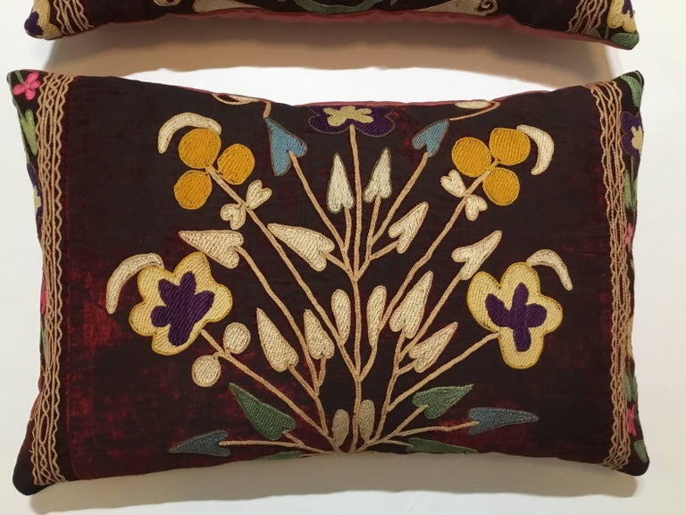 Exceptional pair of pillows made of antique hand embroidery Suzani fragment, beautiful colors of vine and floral motifs all embroidered on a antique oxidized wine color velvet. Quality backing, frash inserts. Great pair for room decoration.