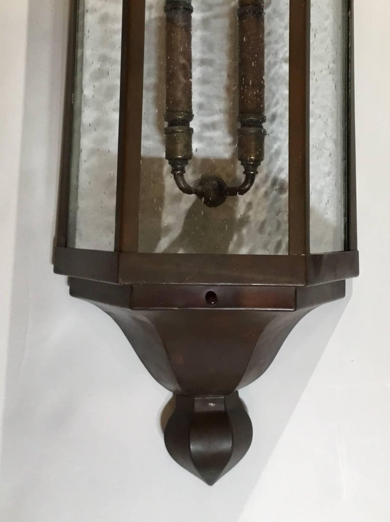 Rescued from a 1930s Art Deco building this large pair of sconces made of copper with seeded glass was restored with custom made steel backplate, treated for rust with one new brass cluster of two 60/watt lights all ready to use. Great pair of